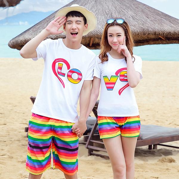 เสื้อคู่รัก ชุดคู่รักเที่ยวทะเลชาย +หญิง เสื้อยืดสีขาวลาย LO VE กางเกงขาสั้นลายแถบสีโทนสีรุ้ง +พร้อมส่ง+